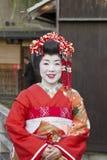 Japansk Geishastående på en röd klänning Arkivfoto