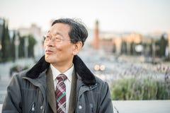 Japansk hög gamal man utomhus le och lycklig stående Arkivfoto