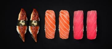 Japansk kokkonst Sushiuppsättning över mörk bakgrund royaltyfri foto