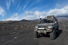 Japansk kryssare Prado för bilToyota land på vulkanisk slagg på bakgrundsvolcanoes royaltyfria foton