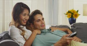 Japansk kvinna och hennes hållande ögonen på tv och skratta för pojkvän Arkivbild