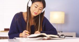 Japansk kvinna som lyssnar till musik, medan göra läxa royaltyfria bilder