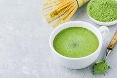 Japansk latte för grönt te för matcha i den vita koppen på grå bakgrund arkivfoton