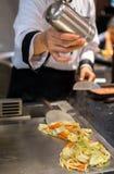 Japansk mat: Den kvinnliga kocken kryddar blandade grönsaker på flamma Arkivbild