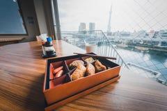 Japansk mat på trätabellen med suddig stadsbakgrund in till Royaltyfria Foton