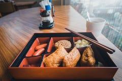 Japansk mat på trätabellen med suddig stadsbakgrund in till Royaltyfri Bild