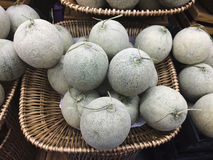 Japansk melon i den wood korgen Arkivfoto