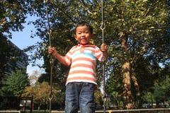 Japansk pojke på en gunga Royaltyfria Bilder