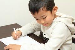 Japansk pojke som gör läxa Arkivfoton