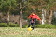 Japansk pojke som sparkar en gul boll Royaltyfri Bild