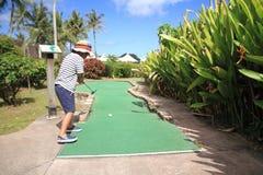 Japansk pojke som spelar med att sätta golf Royaltyfria Bilder