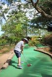 Japansk pojke som spelar med att sätta golf Arkivbild