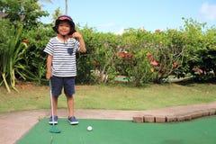 Japansk pojke som spelar med att sätta golf Royaltyfria Foton