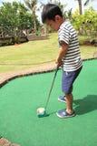 Japansk pojke som spelar med att sätta golf Arkivfoto