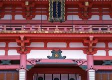Japansk röd, guld- och vit ingångsarkitektur av templet med ledstångdetaljer arkivfoto