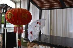 Japansk röd lykta i ett rum med det vita gardin- och vitbröllopparaplyet Arkivbilder