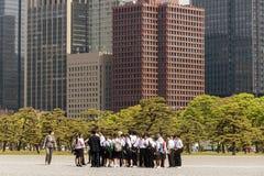 Japansk skolagrupp som besöker den imperialistiska slotten i Tokyo med skyskraporna av Chiyoda, Japan i bakgrunden arkivbilder