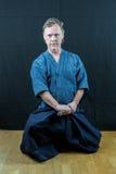 Japansk sport för Caucasian manlig utbildning, iaido Sitta på golv omkring som drar ett svärd royaltyfri bild