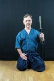 Japansk sport för Caucasian manlig utbildning, iaido Sitta på golvet som rymmer ett japanskt svärd fotografering för bildbyråer