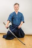 Japansk sportiaido för vuxen caucasian manlig utbildning, sammanträde på golvet med ett utdraget svärd royaltyfri foto