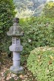 Japansk stenlykta i trädgård Arkivbild