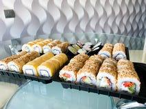 Japansk sushiupps?ttning Uppsättning av sushirullar i en plast- ask, levererat hem klart att äta snabb sund mat arkivbild