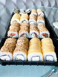 Japansk sushiupps?ttning Upps?ttning av sushirullar i en plast- ask, levererat hem klart att ?ta snabb sund mat royaltyfri bild