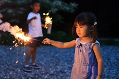 Japansk syskongrupp som gör handheld fyrverkerier fotografering för bildbyråer