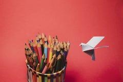 Japansk traditionell origamifågel med en grupp av färgrika blyertspennor arkivfoto