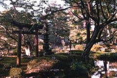 Japansk Zenträdgård med en port och pagod i den Kenrokuen trädgården Kanazawa royaltyfri fotografi