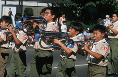 Japanska amerikanska pojkscouter som leker instrument Royaltyfri Foto