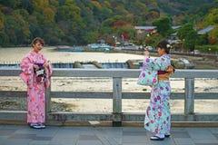 Japanska flickor som tar fotoet på den Togetsukyo bron Arkivbild