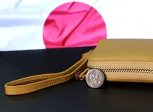 Japanska hundra yenmynt på aversSakura blomningar med sandfärgplånboken på svart golv- och Japan flaggabakgrund fotografering för bildbyråer