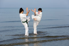 Japanska karateflickor som utbildar på stranden Royaltyfria Foton