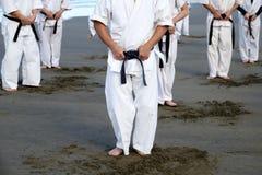 Japanska karatekampsporter som utbildar på stranden Royaltyfria Bilder