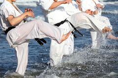 Japanska karatekampsporter som utbildar på stranden Arkivbild