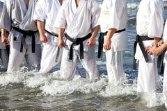 Japanska karatekampsporter som utbildar på stranden Royaltyfri Bild