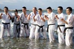 Japanska karatekampsporter som utbildar på stranden Royaltyfria Foton