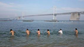 Japanska karatekampsporter som utbildar på stranden lager videofilmer