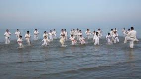Japanska karatekampsporter som utbildar på stranden arkivfilmer