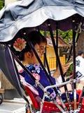 Japanska kvinnor som rider en rickshaw fotografering för bildbyråer