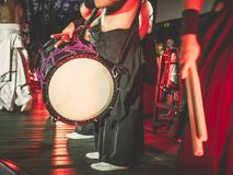 Japanska musiker spelar på Taiko valsnolla-kedo okedo-daiko på en etapp Musikinstrument av Asien royaltyfri foto