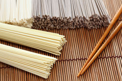 Japanska nudlar med pinnar på bambuservett Fotografering för Bildbyråer