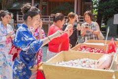 Japanska och asiatiska turister försöker deras lycka, genom att agna som är lyckligt för Arkivbild