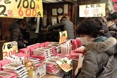 Japanska shoppare granskar gods i en stall i Asakusa, Japan Arkivbilder