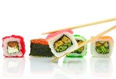 Japanska sushi och pinnar på vitbakgrund Royaltyfria Foton
