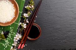 Japanska sushipinnar över soya bowlar, ris och sakura b arkivfoton