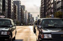 Japanska taxitaxiar väntar på en tvärgata i Akusaka, Tokyo, Japan Fotografering för Bildbyråer