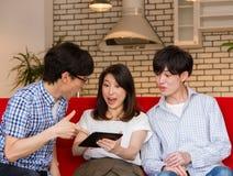 Japanska ungdomar, som att hålla ögonen på tillfredsställer på internet med minnestavlaapparaten som talar och skrattar arkivbild