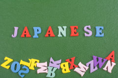 JAPANSKT ord på grön bakgrund som komponeras från träbokstäver för färgrikt abc-alfabetkvarter, kopieringsutrymme för annonstext Royaltyfria Bilder